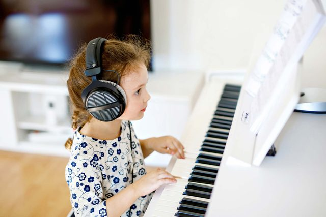 little girl playing keyboard piano
