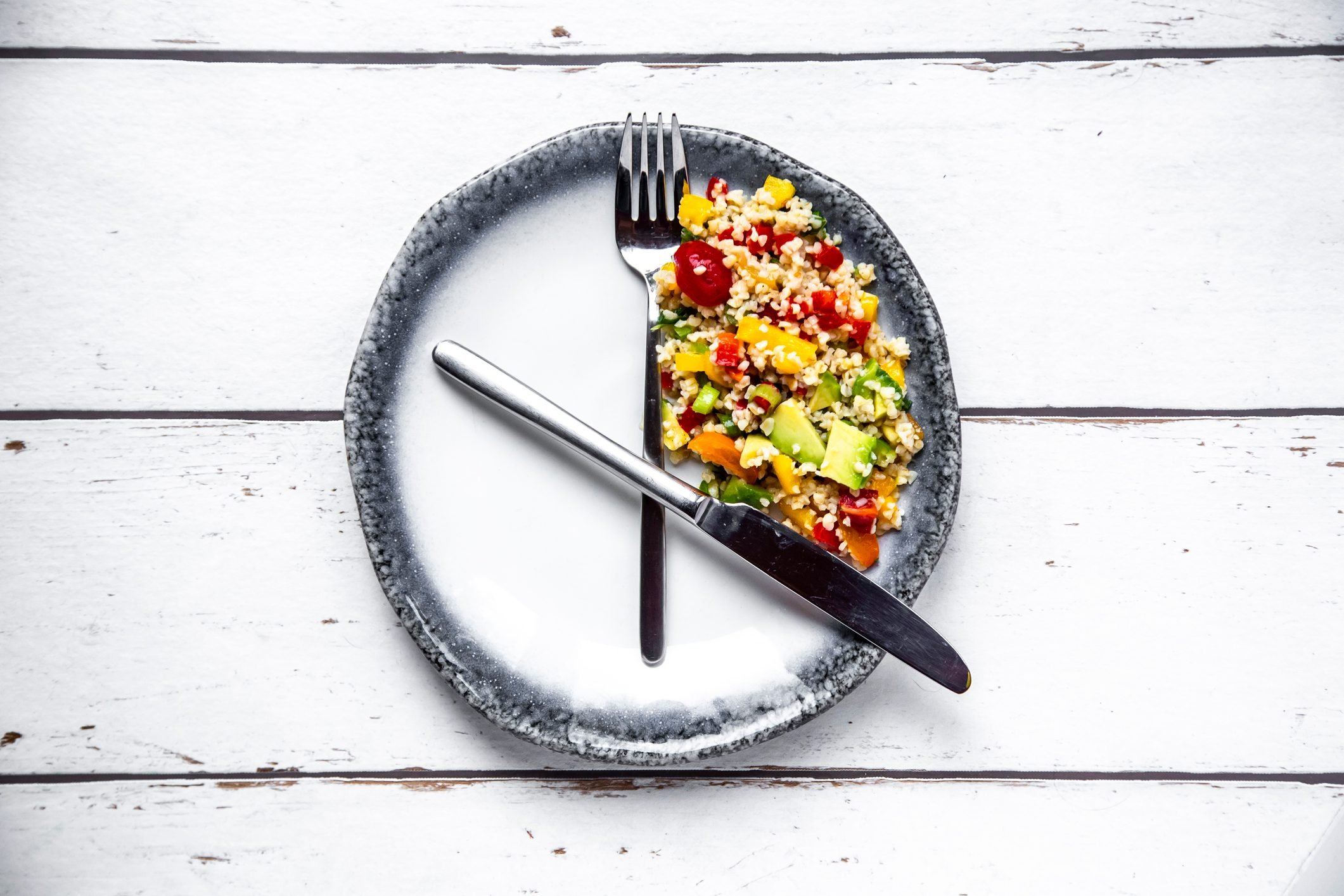 plate with fork and knife resembling a clock for intermittent fasting concept