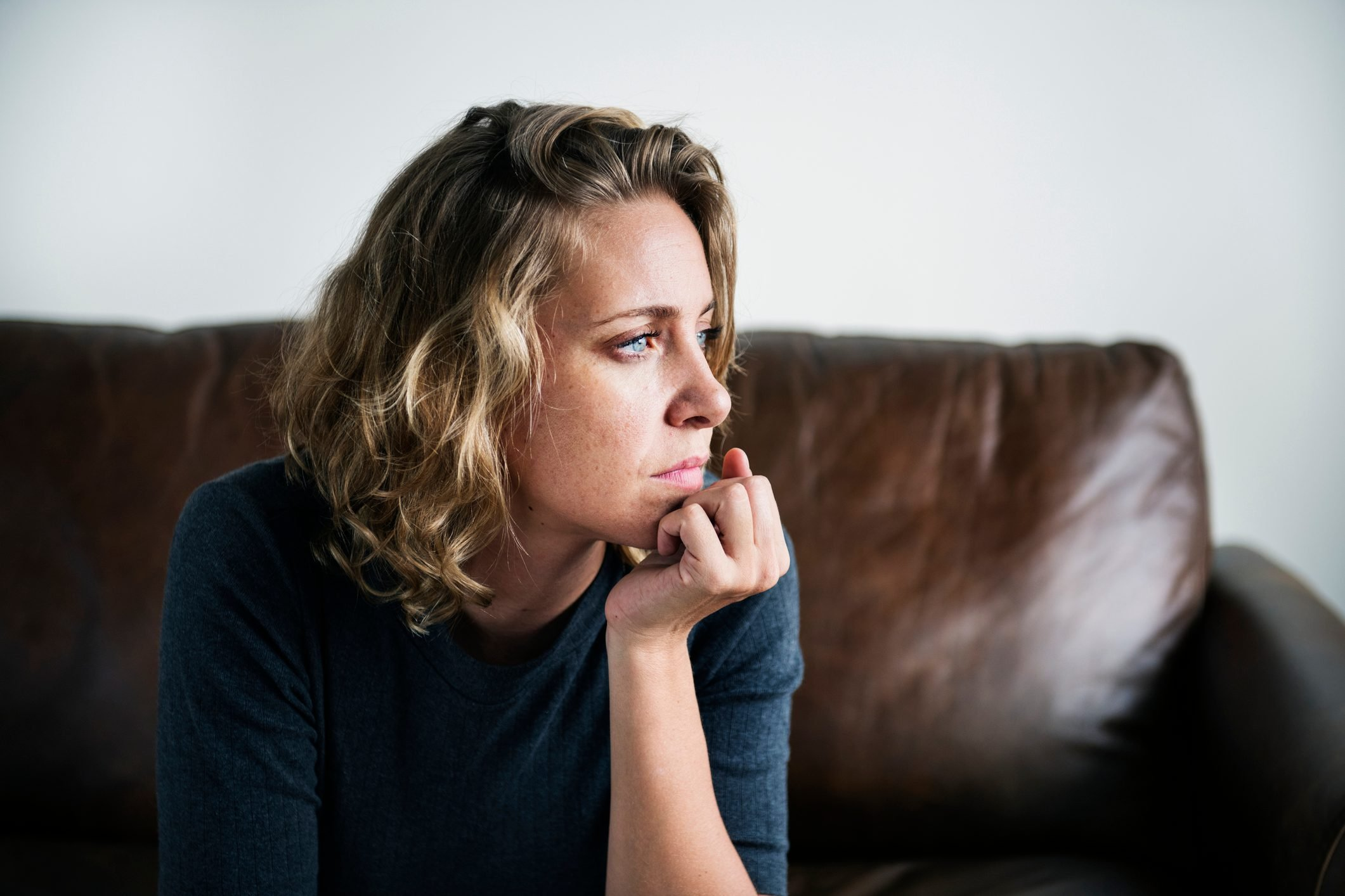 woman sitting on sofa sad