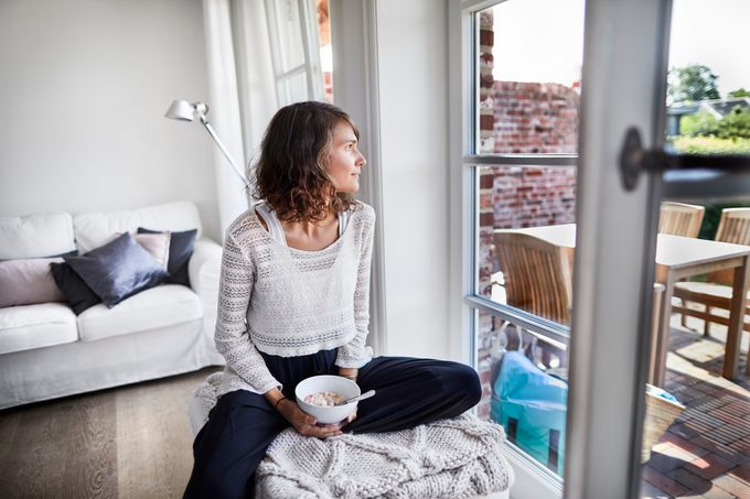 woman sitting at home eating lunch and looking out the window