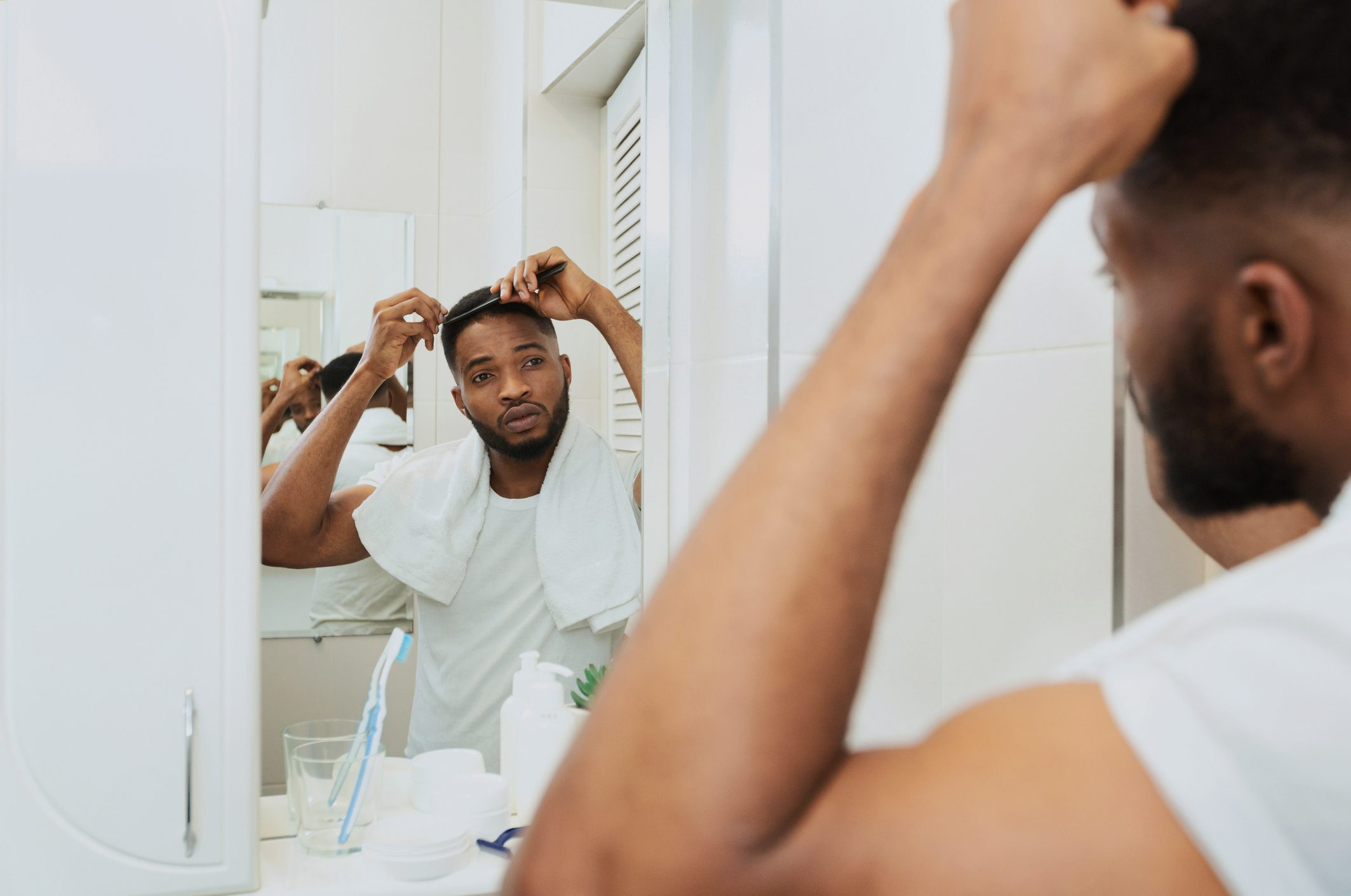 man examining hair in bathroom mirror