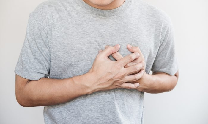 cropped shot of man holding his chest from pain