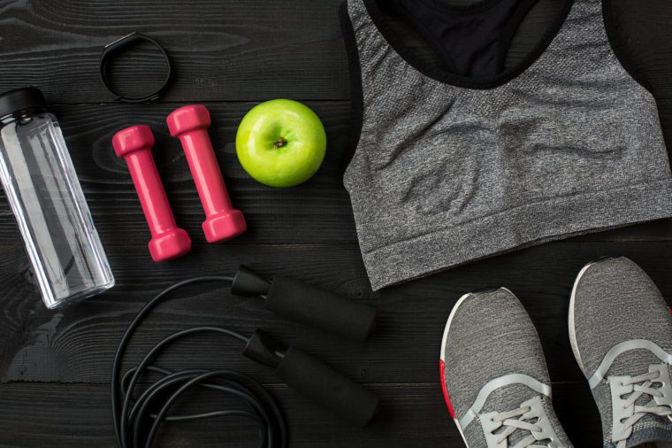 Sports equipment and wear on dark wooden background, top view