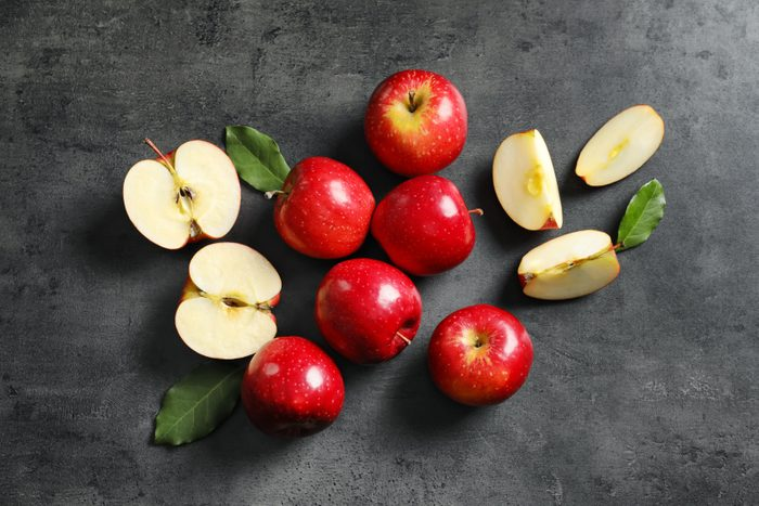 Whole, halved, and quartered red apples