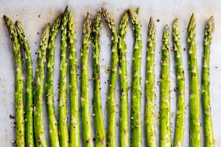 Asparagus spears on parchment paper over oven tray