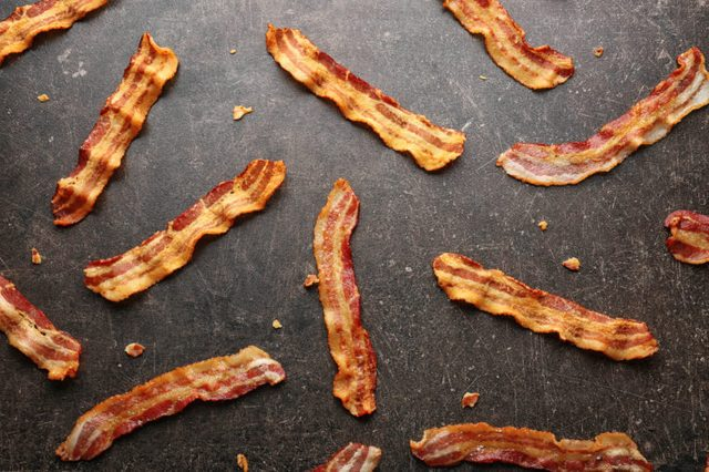 Strips of fried bacon on gray background