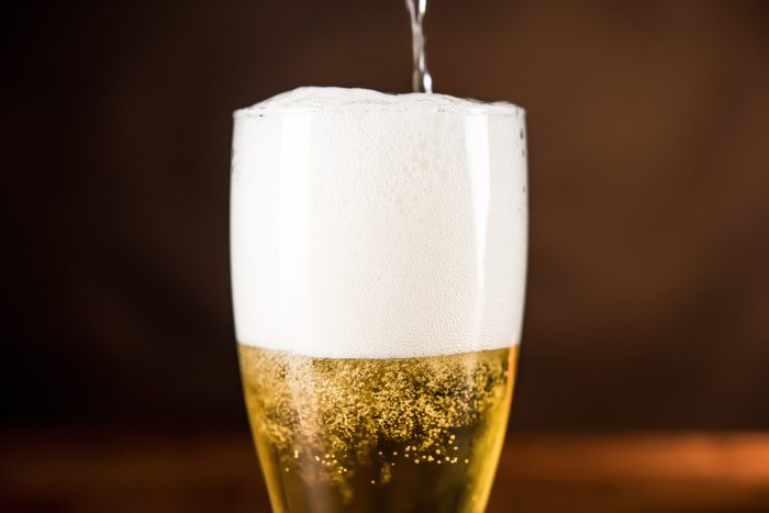 Golden cold beer being poured into the glass with frothy foam