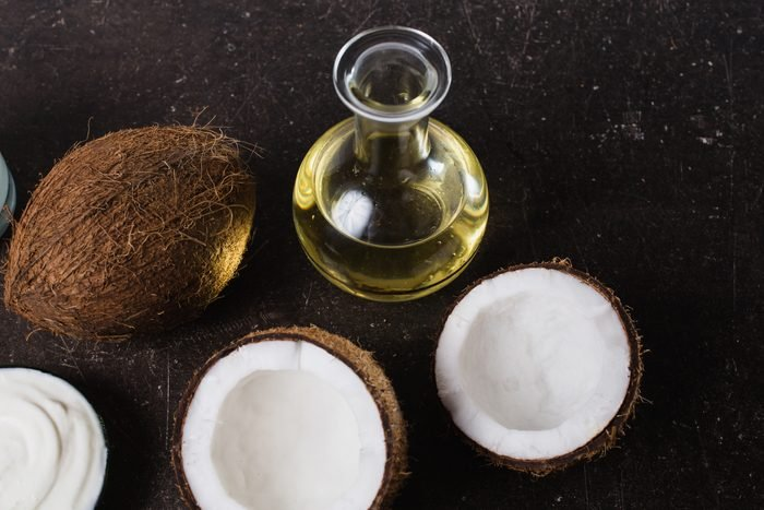 Coconut and coconut oil on a dark marble background. Exotic large walnut. Personal care. Spa treatments