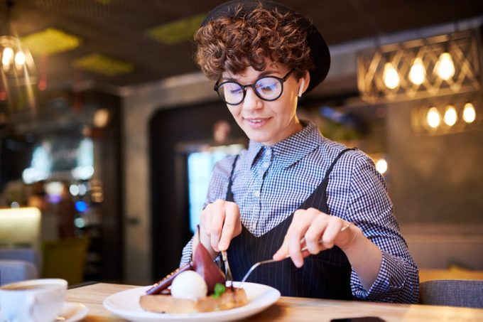 Young woman taking piece of pear dessert off her plate while sitting in cafe at lunch break