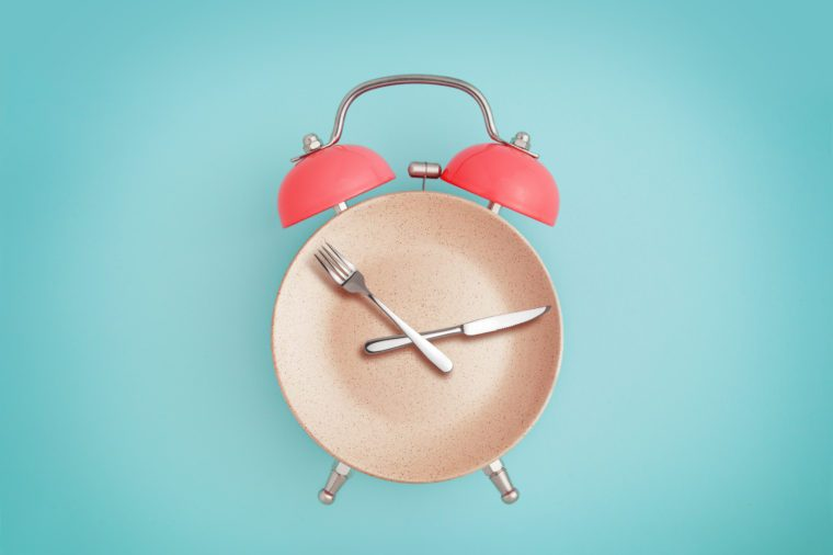 Alarm clock and plate with cutlery . Concept of intermittent fasting, lunchtime, diet and weight loss