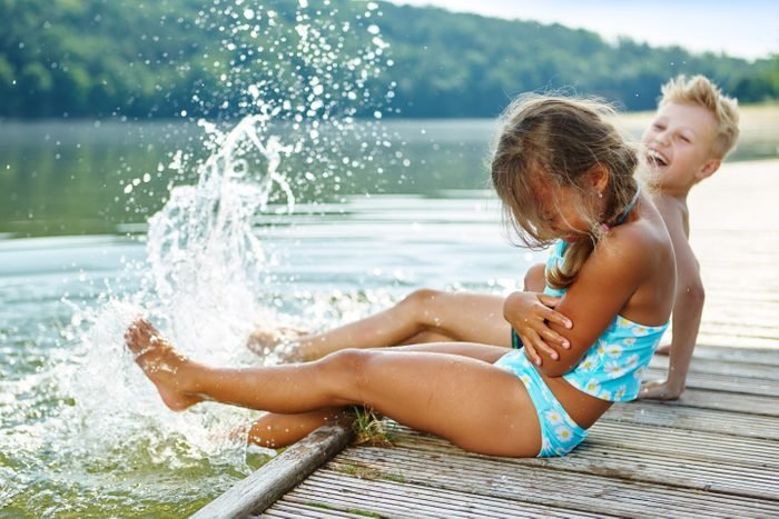 Two kids splashing water with their feet in summer