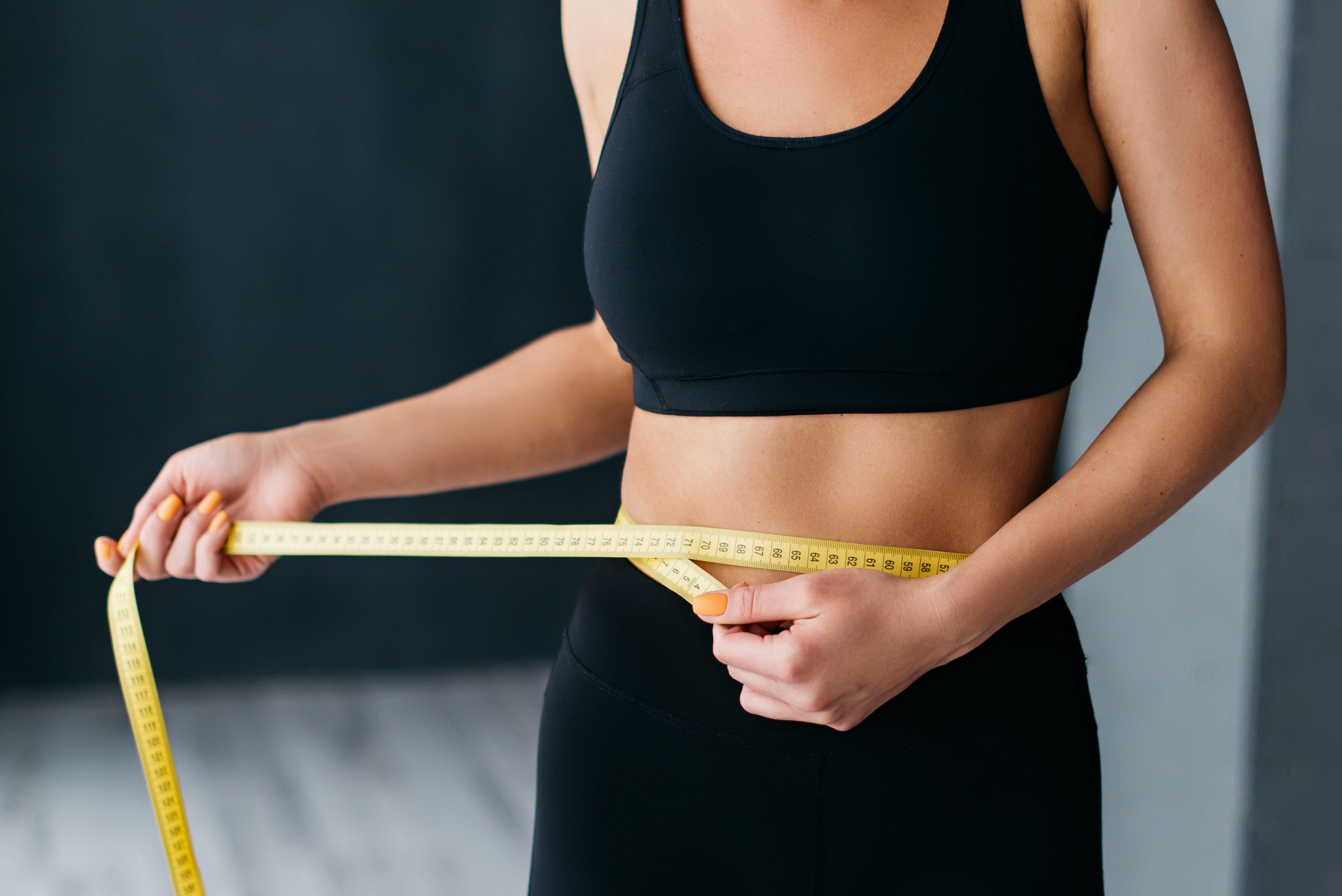 Woman in black sports bra and leggings measuring her waist
