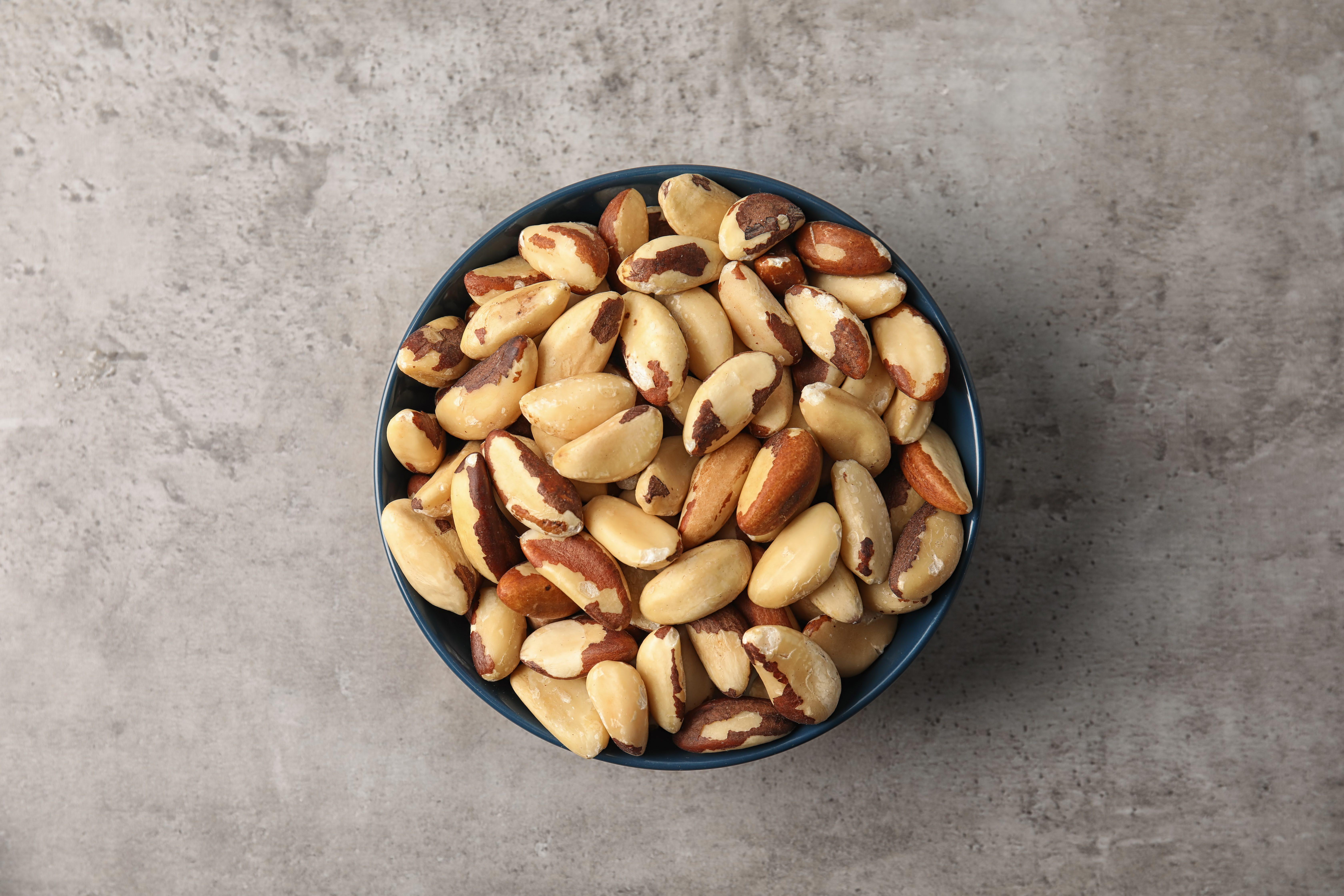 Blue bowl full of shelled Brazil nuts