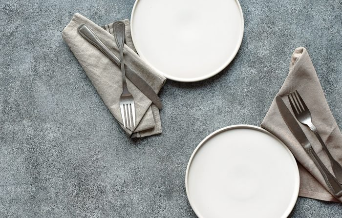 Two white plates, cloth napkins, and silverware on a slate background