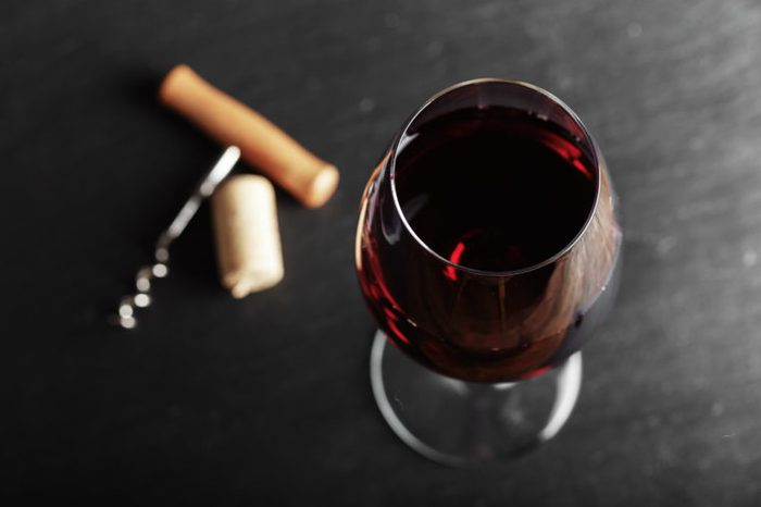 wine glass of red wine with a corkscrew. On a black wooden background.