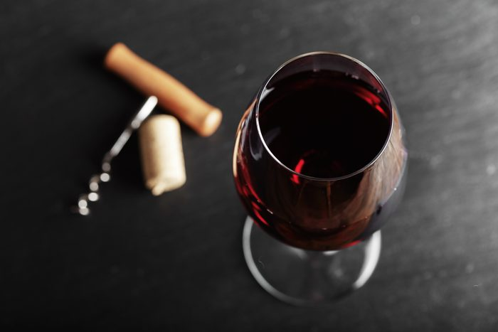 wine glass of red wine with a corkscrew