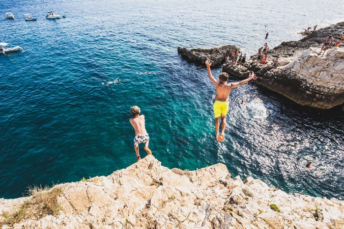 Two children diving from a cliff