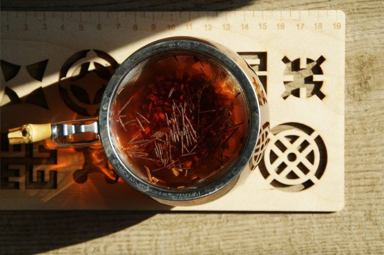 A glass cup with red-coloured wild Rooibos tea, wooden tea tray with geometrical shapes carved out, light brown pavement, sun and shadows.