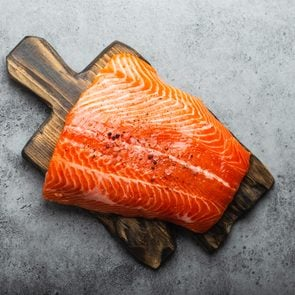 Top view, close-up of whole  fresh raw salmon fillet with seasonings on wooden board, gray stone background. Preparing salmon fillet for cooking, healthy eating concept