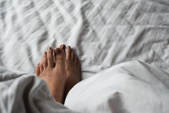 Close up of the feet of a young lady on the bed under white blanket. Foot tip beetle from blanket when lying in bed enjoying sensual foreplay. Holiday and relax concept.