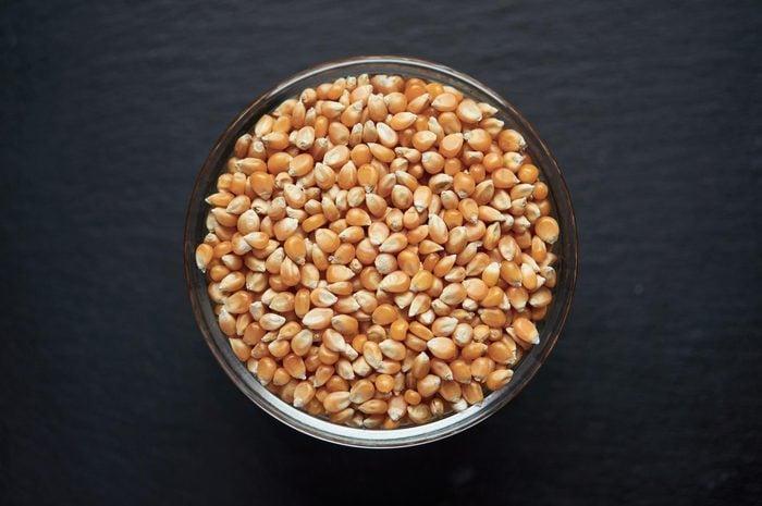 Corn kernels in a bowl on dark background