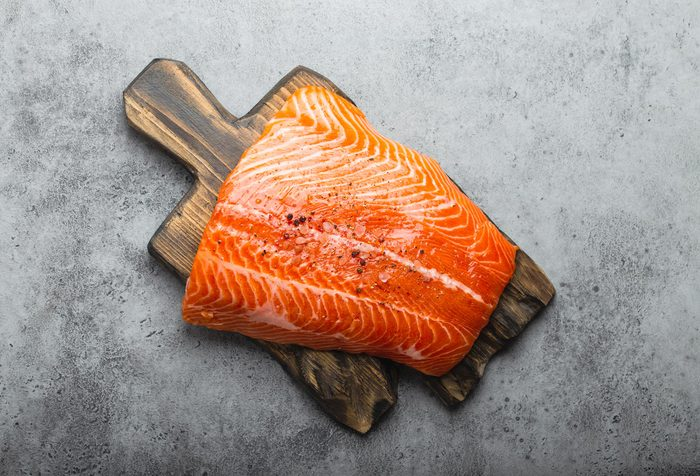 whole fresh raw salmon fillet with seasonings on wooden board