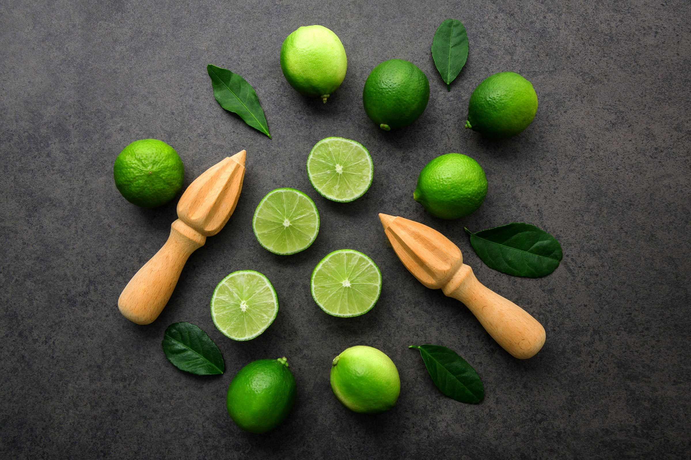 Fresh limes and wooden juicer