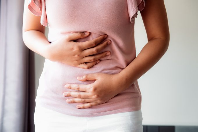 Woman is Having Stomach Ache or Menstrual Period, Close-Up Portrait of Young Woman is Suffering From Abdominal Pain at Her Home. Healthcare and Medicine Concept.
