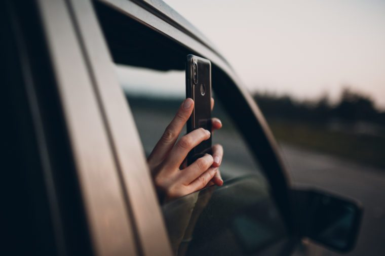 Girl takes pictures on the phone from the car window
