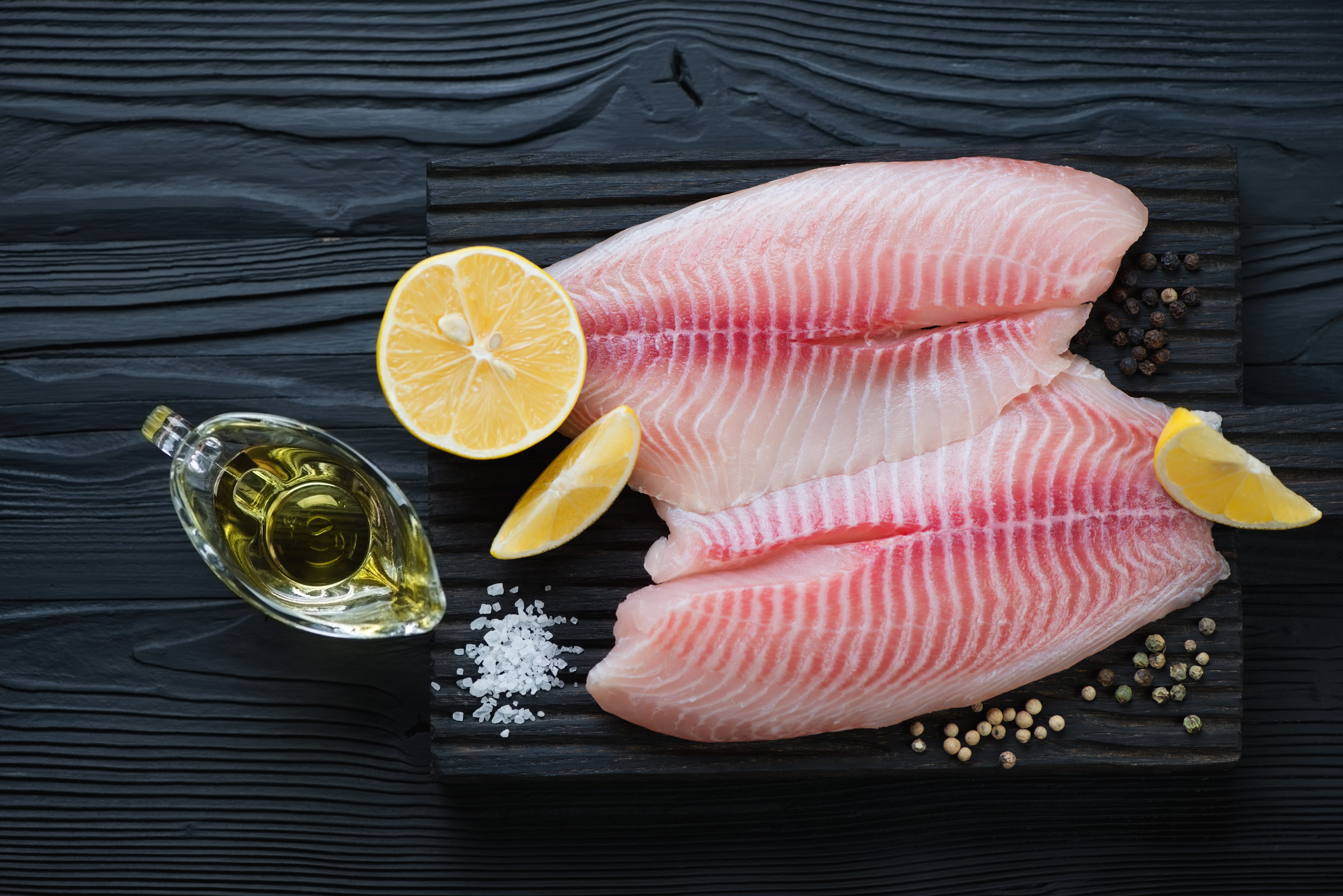 Fresh tilapia fillet ready to be cooked, black wooden background, top view