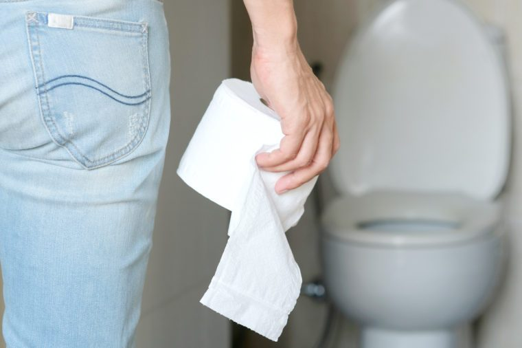 Man's hand holding a roll of toilet paper with toilet in background