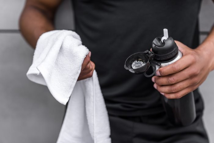cropped shot of young african american sportsman holding sports bottle and towel