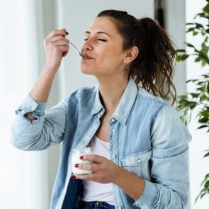Portrait of beautiful young woman eating yogurt at home.