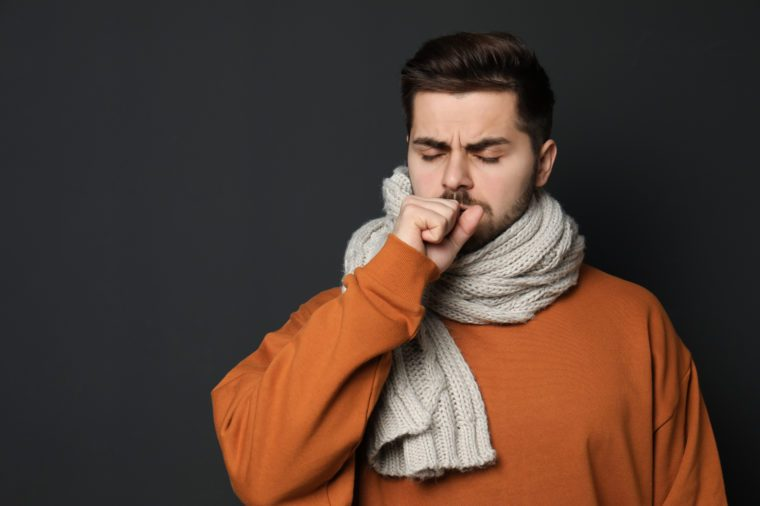 Handsome young man coughing against dark background. Space for text