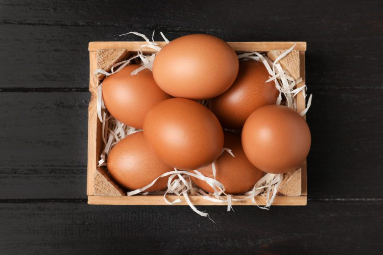 Wooden crate full of fresh eggs on dark background, top view