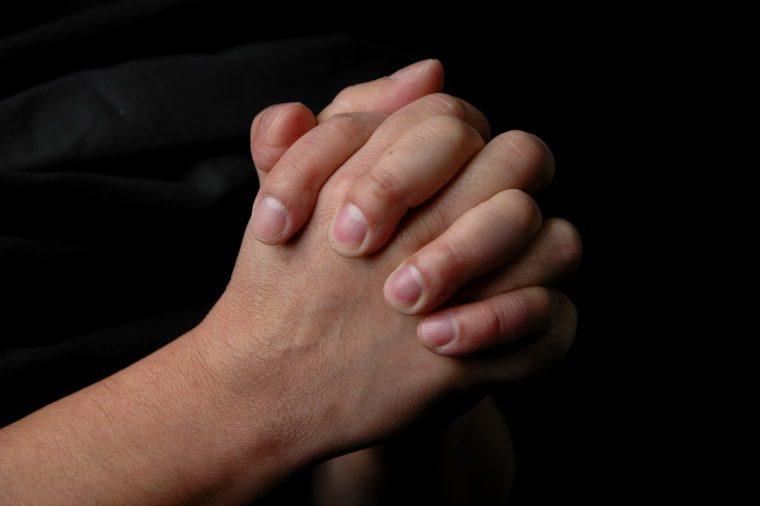 Hands in prayer on dark background