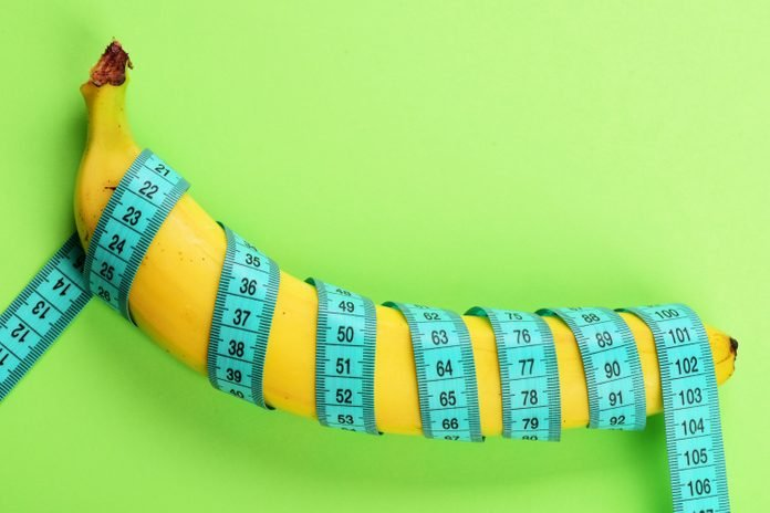 Banana with blue tape for measuring figure. Centimeter ruler spinned around fruit. Blue tape wrapped around banana isolated on light green background. Weight loss, healthy food and slim body concept.