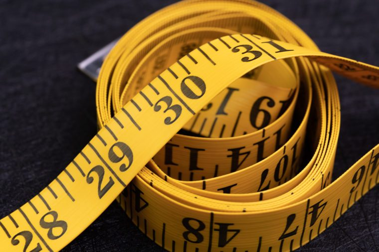 Exercise, health and diet concept, role of yellow measuring tape on dark black background with copy space.