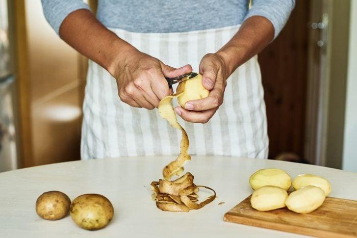 Peeling some potatoes on white table
