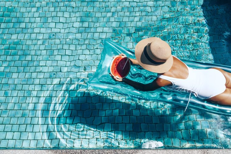 Girl floating on beach mattress and eating watermelon in the blue pool. Tropical fruit diet. Summer holiday idyllic. Top view.