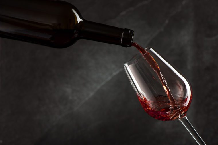 Wine pouring from bottle on dark background