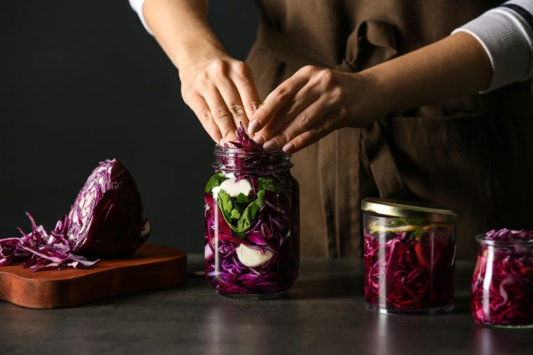 Woman preparing fresh cabbage for fermentation on table