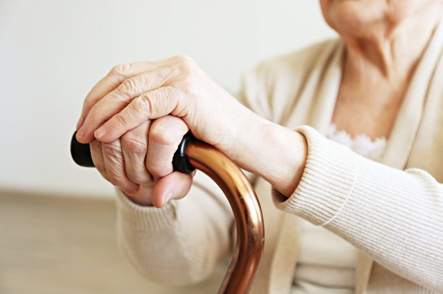 Elderly woman sitting in nursing home room holding walking quad cane with wrinked hand. Old age senior lady wearing beige cardigan, metal aid stick handle bar close up. Interior background, copy space