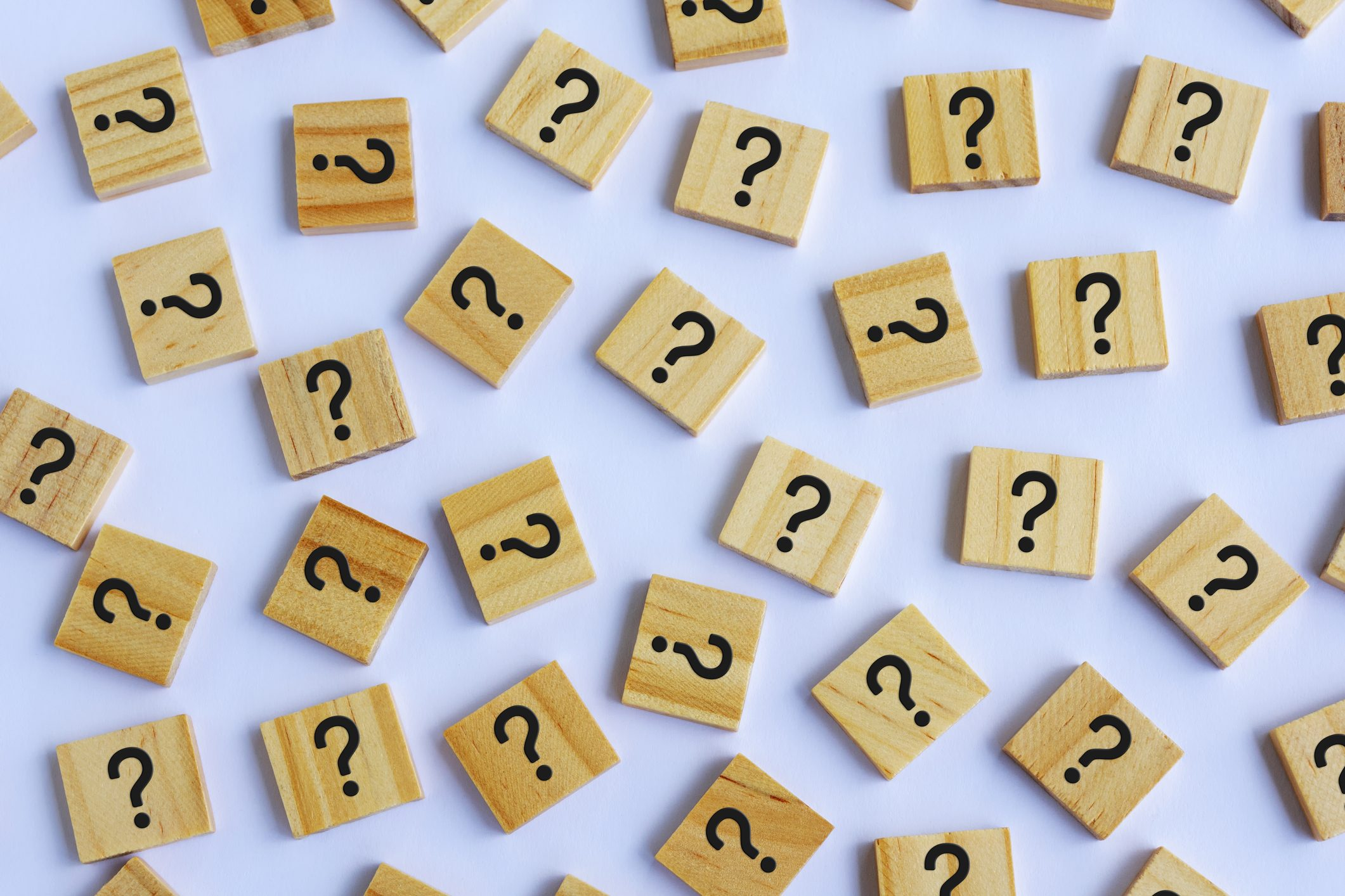 wooden blocks with question marks on light purple background