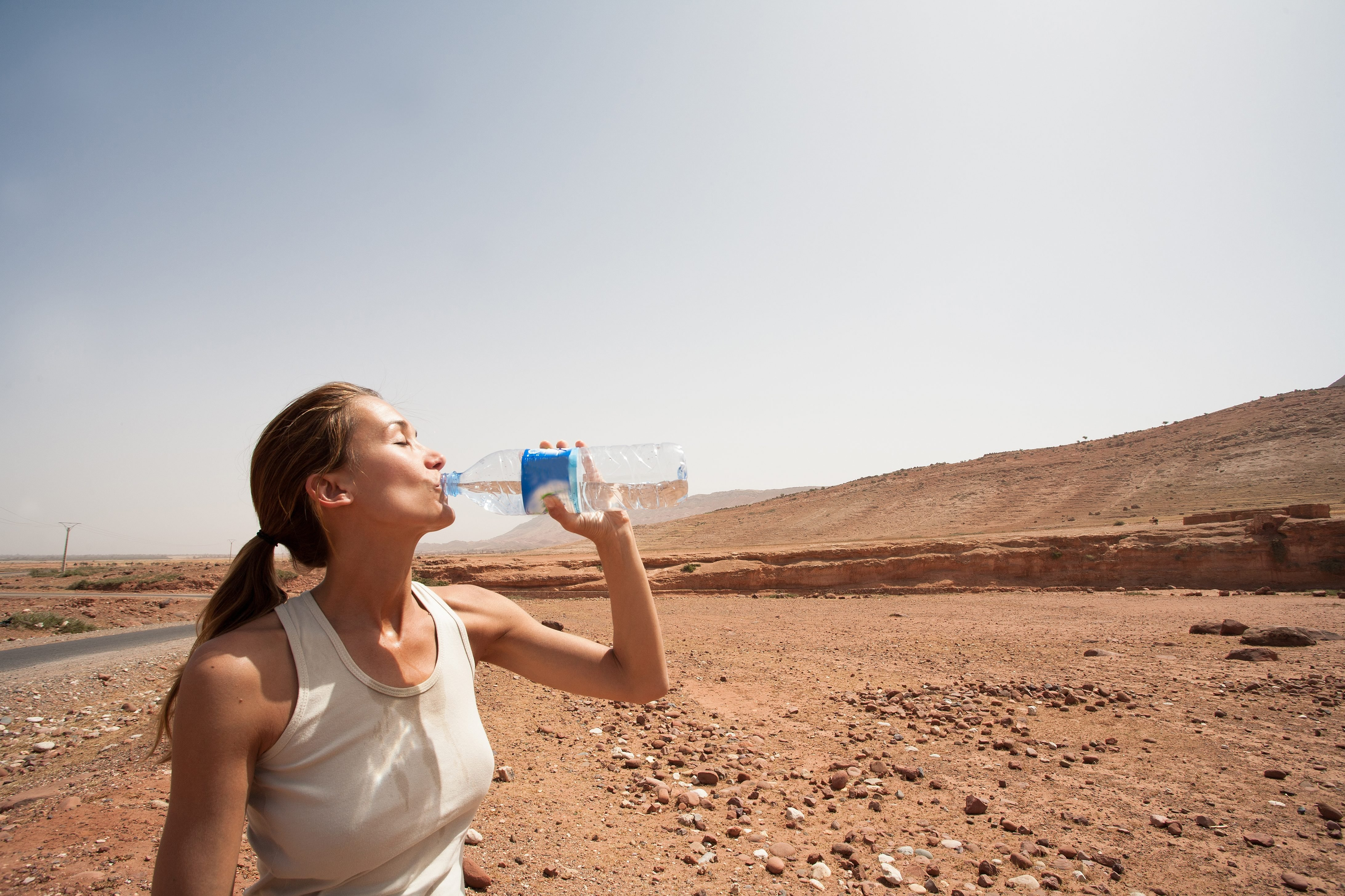 woman drinking water in the desert
