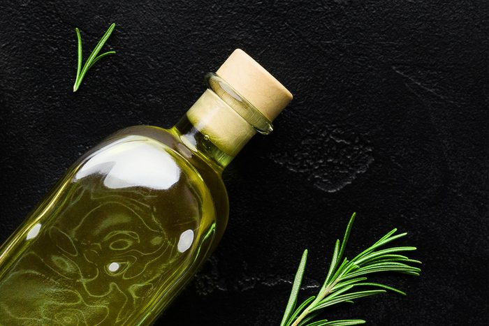 Olive oil in bottle , fresh olives and rosemary sprigs on black background, top view. Organic olive oil concept