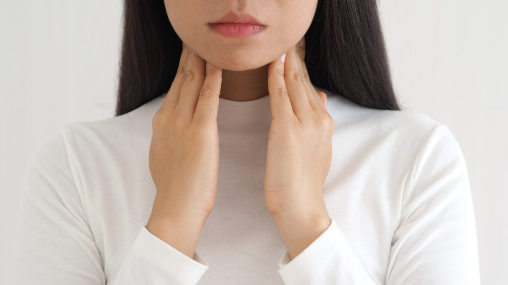 thyroid gland,hyperthyroidism and tonsillolith or tonsil stones and laryngeal cancer in asian woman. She use hand touching neck on isolated white background using for health care concept.