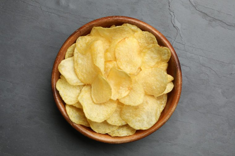 Bowl of potato chips on grey table, top view