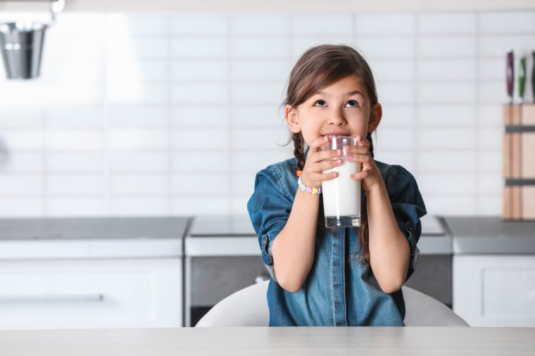 Cute little girl drinking milk at table in kitchen