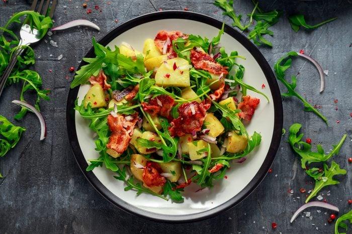 Fresh crispy Bacon, Potato salad with green vegetable on plate